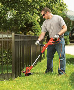 a man trimming grass around a fence using the GH900