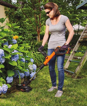 lady trimming around shrubs using the LSTE523