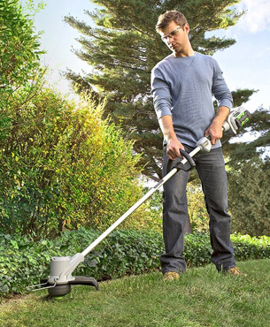 a man trimming grass on his garden using the EGO Power+ 56-Volt trimmer