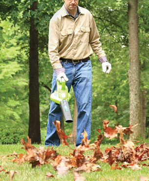 man using the blower to get rid of leaves