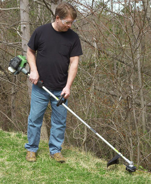 a man trimming grass on his garden using the CG22EAP2SL