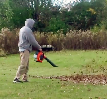 man blowing leaves from grass
