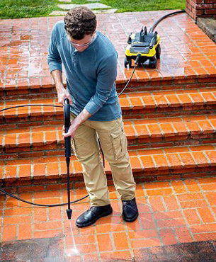 a man cleaning a floor using the K 3.000