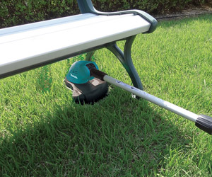 using the tilting head to trim grass under a bench