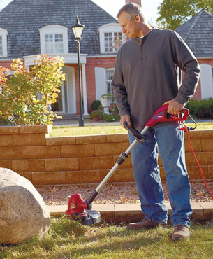 a man trimming grass on his garden using the Toro 51480